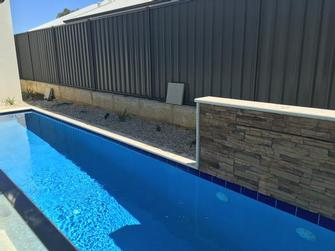 The pebbles have been removed and rainbow stone has been laid to give a low maintenance and clean garden bed around the pool in Banksia Grove